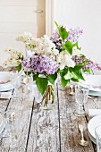 Spring dining table festively set with vase of lilac