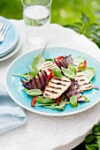Grilled haloumi and red onions on a vegetable and lettuce salad