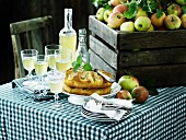 An arrangement of apples featuring apple juice and apple cake on a table laid with a checked cloth