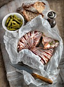 A rustic terrine wrapped in bacon with gherkins and bread