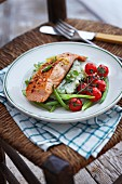 Salmon fillet on mushy peas with cherry tomatoes