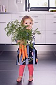 A little girl holding a large bundle of carrots