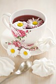 Daisies floating in tea in floral teacup