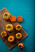 Persimmons, whole and halved
