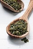 Organic pumpkin seeds on wooden spoons