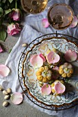 Pistachio and rose cakes decorated with flower petals (seen from above)