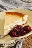 A cheesecake with white chocolate and berry sauce