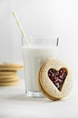 A heart-shaped jam sandwich biscuits in front of a glass of milk