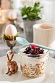 Muesli and berries in screw-top jar with spoon and hare ornament on plate