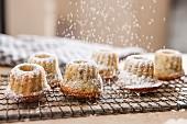 Dusting mini poppyseed bundt cakes with icing sugar