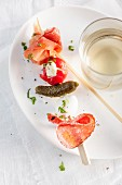 An antipasti skewer and white wine on white plate