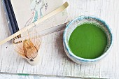Matcha in a bowl (chawan), next to a bamboo whisk (chasen) and a spoon (chashaku)