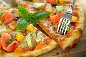 Pizza with salmon, squid, avocado and mango