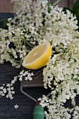 Half a lemon on a grater and elderflowers
