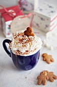Hot chocolate topped with cream and gingerbread biscuits