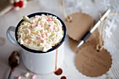 Hot chocolate in an enamel mug with cream and marshmallows