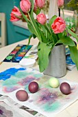 Painted Easter eggs on paper in front of metal vase of pink tulips