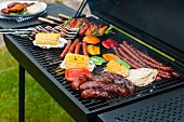 Sausages, skewers and vegetables on a charcoal barbecue