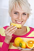 A young blonde woman with a slice of pineapple and a plate of citrus fruits
