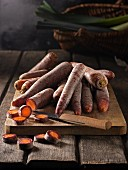 Purple carrots on a wooden chopping board