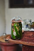 A jar of homemade gherkins with spices on a table