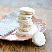 A stack of macaroons on a plate with one leaning against a plate