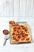 A salami, pepper and caper pizza