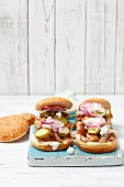 Burgers with pork, gherkins, horseradish cream sauce, red onions and feta cheese