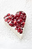 A white chocolate heart with pomegranate seeds in a mold