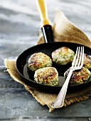 Fish meatballs with chilli and dill in a frying pan