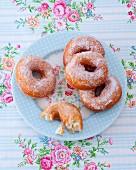 Gezuckerte Doughnuts auf geblümten Teller