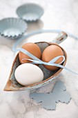 Hen's eggs with a ribbon in a small wooden scoop on a marble surface