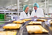 Quality-control workers checking cheese on a conveyor belt