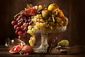 An autumnal fruit bowl featuring grapes, pears, persimmons and pomegranates