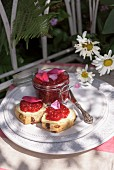 Currant buns topped with raspberry jam and rose petals on a garden table