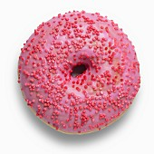 A pink doughnut decorated with red sugar sprinkles