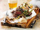 Grilled beef steak with spring onions and mustard on a chopping board
