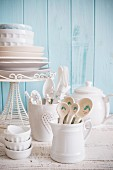 White crockery and cutlery against a light blue wooden wall