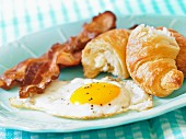 A fried egg with bacon and a croissant