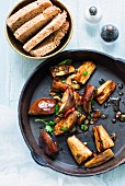 Fried aubergines with chillis in the pan