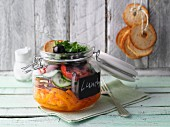 Layered spicy vegetable and bread salad in a jar