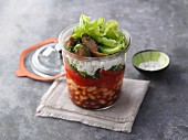 Layered pepper and bean salad with feta cheese in a jar