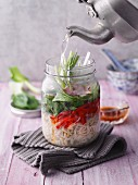 Sweet-and-sour soup with ham and bok choy in a jar being filled with water