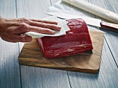 A piece of beef being patted with kitchen paper