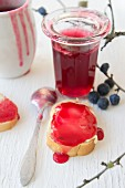 Sloe jelly in a glass and on a piece of bread