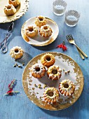 Mini Bundt cakes on gold-patterned plates on a blue wooden surface