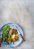 Lamb chops on potatoes, asparagus and peas