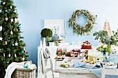 Weihnachtstisch mit Kuchen und Keksen neben dem Christbaum