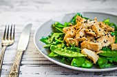Grilled chicken with spinach, rocket and peas
