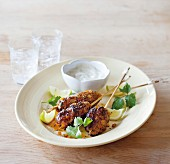 Pork skewers with curry and apricots served with yoghurt sauce